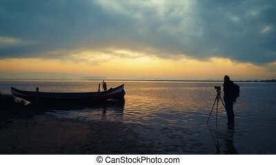 Photographer in action shooting sunrise moment near moored...