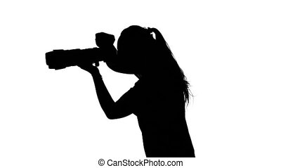 Photographer in studio conducts photography. White. Silhouette