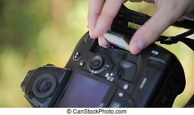 Photographer inserting memory card in camera