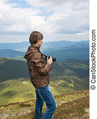Photographer is shooting landscapes on a mountain top.