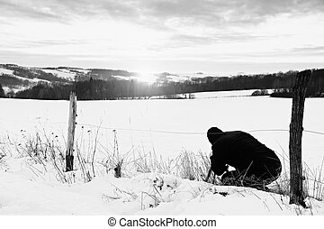 Photographer lay in snow on meadow and takes a picture of fantastic sunset above hill