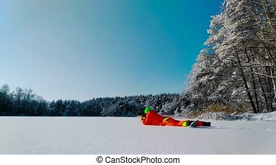 Photographer laying on a surface of frozen lake -...
