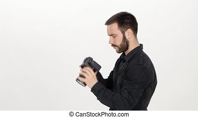 Photographer takes photos on camera, a young man stands in profile and he holds a camera, man trying to get a good picture, on white background