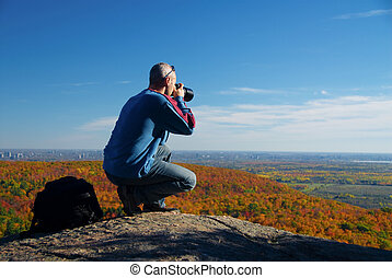 Photographer - male photographer shooting at the top of a...