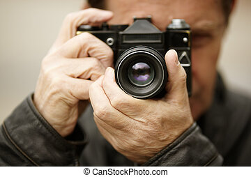 man with retro film camera, natural sunset light, selective focus on nearest part of the lens