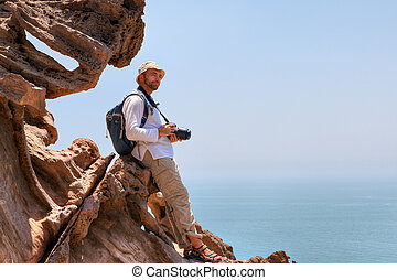 Photographer of nature resting on a rock while traveling, Iran.