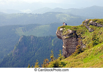 Photographer taking photo from a huge rock in the mountains