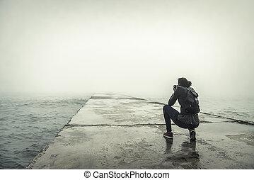 Photographer on a misty pier. Vintage photo.