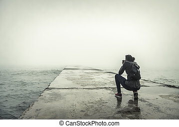 Photographer on a misty pier.
