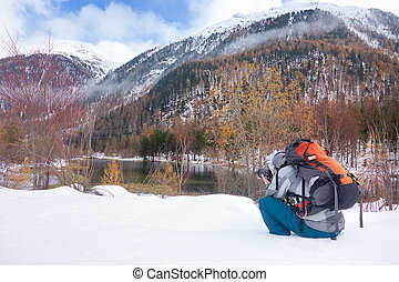 Photographer on the snow in autumn in front of a mountain lake