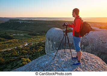 Photographer on top of mountain at sunset