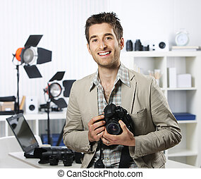 Portrait of young male photographer with professional digital camera