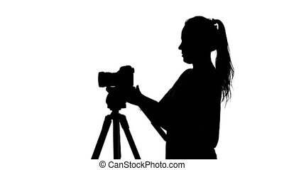 Photographer puts the camera on a tripod. White. Silhouette...