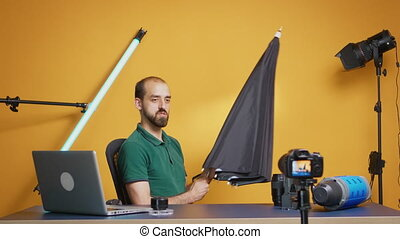 Professional photographer recording umbrella review in studio. Professional studio video and photo equipment technology for work, photo studio social media star and influencer