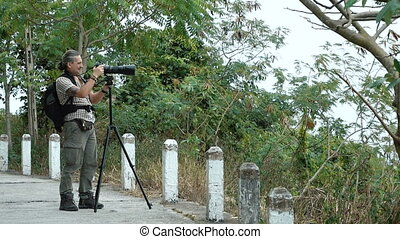 Photographer shoots on a telephoto lens using tripod. Full...