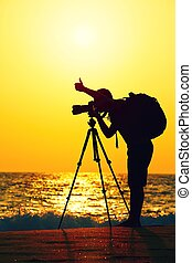 Photographer - Silhouette of young photographer on the beach...