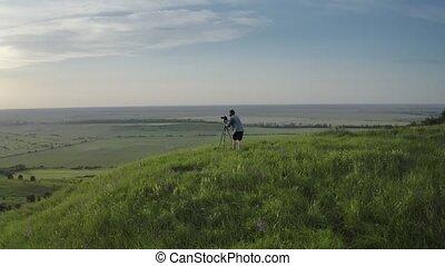 Photographer standing on green hill with tripod and camera...