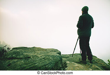 Photographer stay at tripod on summit. Man photographer during hike