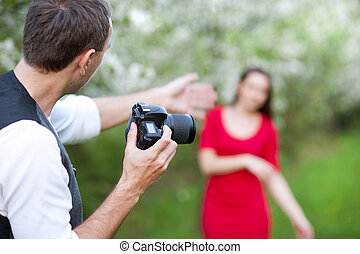 Photographer is taking photos of beautiful woman in red...