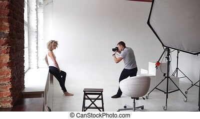 Photographer takes a picture near the window for a young model in the studio