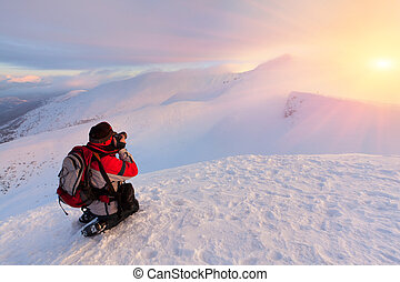 Photographer takes a sunset in the mountains