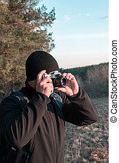 photographer takes photo on film camera