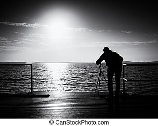 Photographer takes photos with mirror camera and tripod at end of pier board.