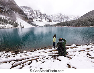 Photographer takes picture of female model next to beautiful lake