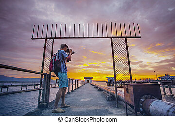 photographer taking a photograph at water work station and sun rising sky background