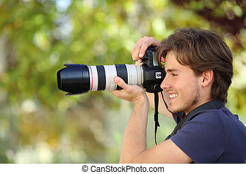 Photographer taking a photograph outdoor with a dslr camera...