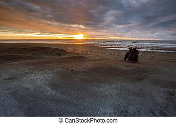 photographer taking a sun set photograph on hokitika beach south island new zealand
