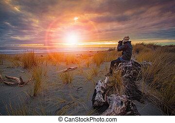 photographer taking a sunset photo on sea beach