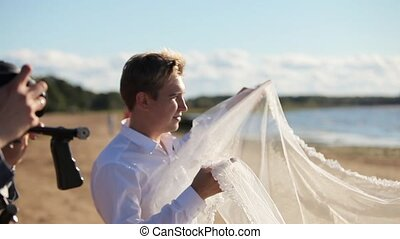 Photographer taking photo of waving bridal veil at the beach