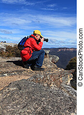 Photographer taking photos of mountain landscape - A ...
