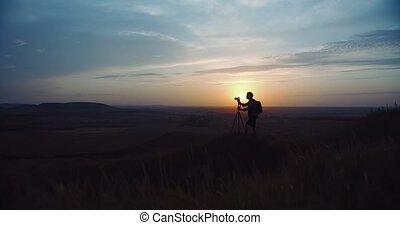 Photographer taking photos of sunset and using tripod - Full...
