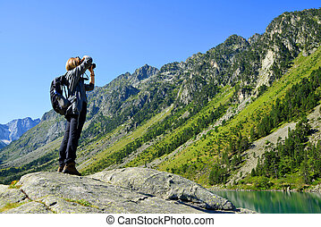 Photographer taking picture photos with DSLR camera at Gaube lake. France.