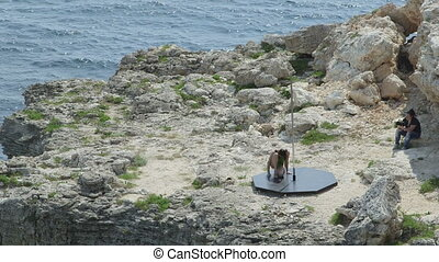 Photographer taking pictures of pole dancer during pole dance on a rock