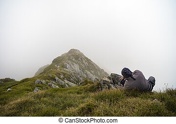 Photographer taking shots at the beautiful mountaineous landscape
