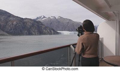 Photographer tourist in Alaska taking photos of glacier national park