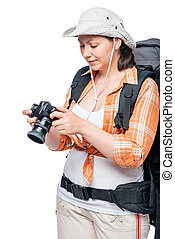 Photographer tourist woman looking at pictures on the camera on a white background