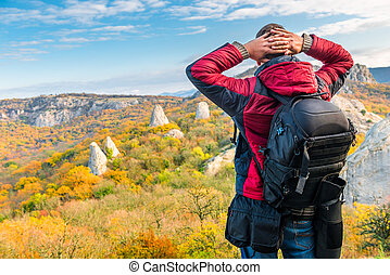Photographer traveler with a backpack admiring beautiful mountains in autumn, rear view