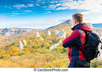 Photographer traveler with a backpack admiring the beautiful mountains in autumn