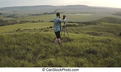 Photographer using tripod and digital camera on hill - ...