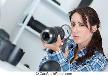 photographer with a magnifying glass looking into lens