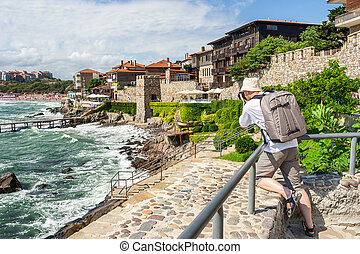 photographer with backpack shooting in old town Sozopol near...