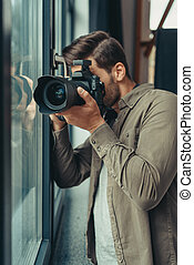 photographer with camera at window
