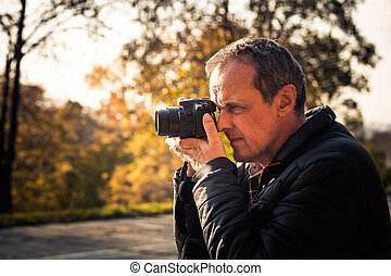 photographer with digital camera outdoor - photographer take...