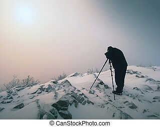 Photographer with eye at viewfinder of camera on tripod stay on snowy cliff and takes photos.