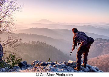 Photographer with tripod and camera on rock thinking.