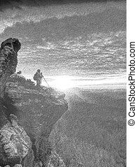 Photographer with tripod in hand. Man hold tripod, stand on rock